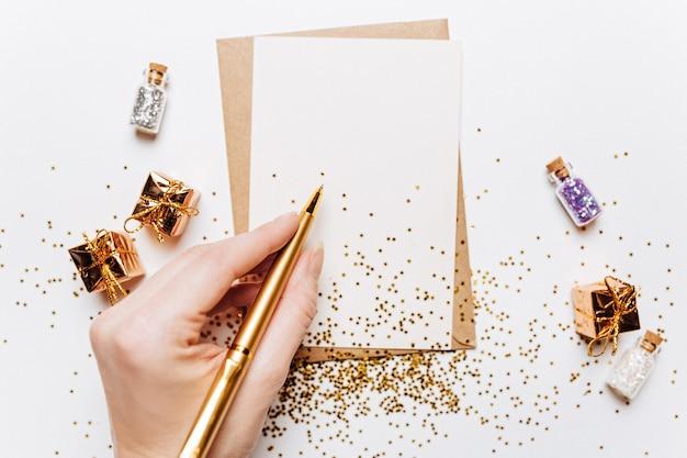 Fille écrit une note vierge avec des cadeaux, un stylo et des étoiles de paillettes d'or sur fond blanc