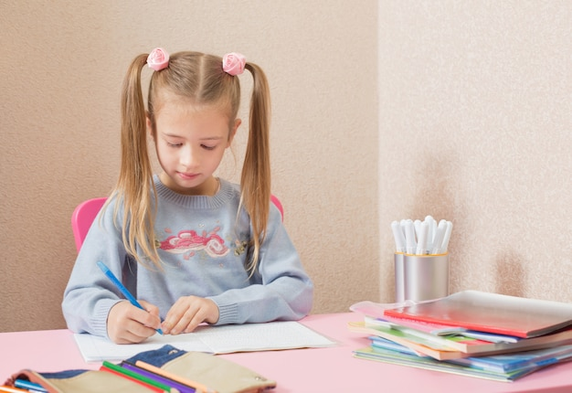 Fille écrit avec un stylo à la table