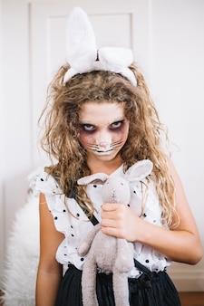 Une fille effrayante avec des oreilles et un jouet de lapin
