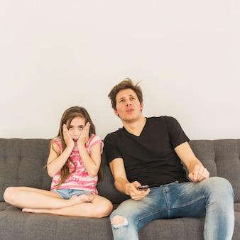 Fille effrayée, assise près de son père sur le canapé