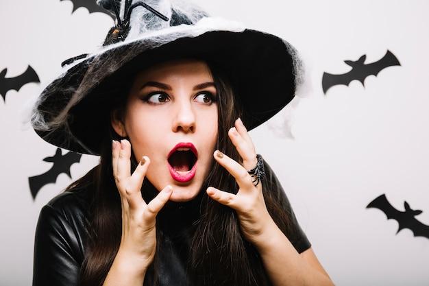 Une fille effrayée avec un chapeau de fête avec un web