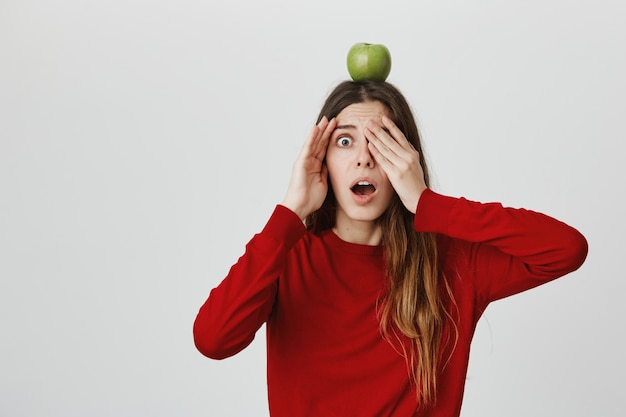 Fille effrayée ouvrir les yeux et laisser tomber la mâchoire inquiète comme quelqu'un tirant une flèche sur une cible de pomme sur sa tête
