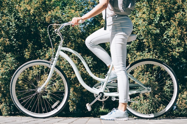 Fille élancée dans un jean t-shirt blanc et des baskets est assis sur son vélo élégant