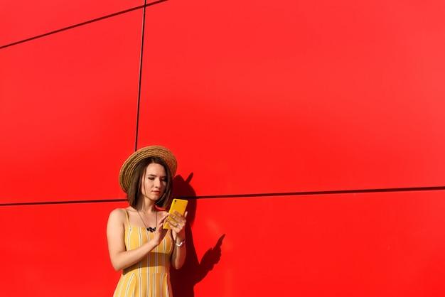 Fille élancée posant contre un mur rouge avec un téléphone