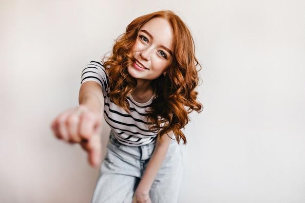 Fille élégante au gingembre en pantalon en denim dansant. portrait de stusio de jeune femme rousse active.