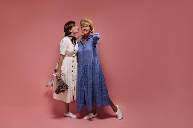 Fille élégante aux cheveux courts en robe blanche tenant des fleurs sauvages et s'embrassant sur la joue à la vieille dame blonde en vêtements bleus et chapeau sur fond rose.
