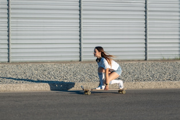 Fille élégante en bas blancs monter sur longboard dans la rue