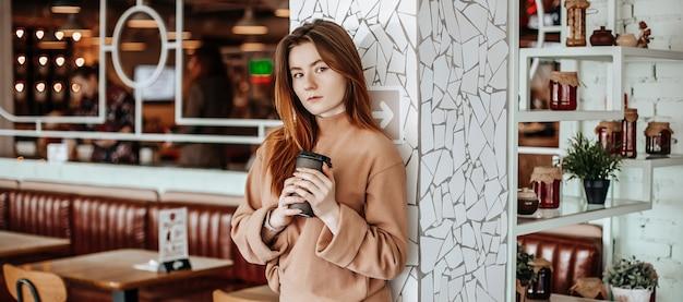 Fille élégante boit du café dans un café