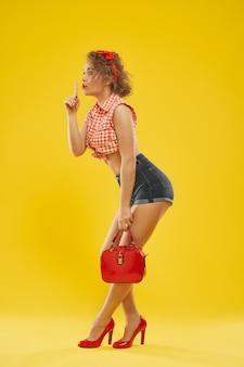 Fille élégante en chaussures à talons rouges avec petit sac rouge.
