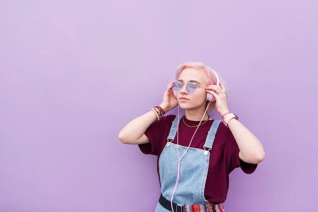 Une fille élégante avec des cheveux roses et des lunettes de soleil apporte de la musique au casque