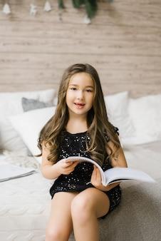 Fille élégante de cinq ou six ans vêtue d'une robe noire avec des paillettes se retournant et lisant un livre ou un magazine