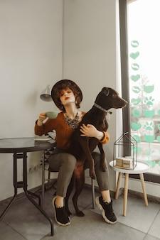 Fille élégante dans un chapeau et aux cheveux bouclés tient une tasse de café et câlins chien dans un café léger et confortable