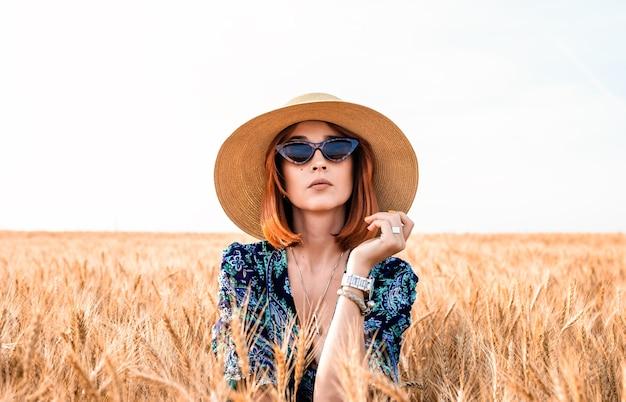 Fille élégante dans un chapeau sur fond d'épis de blé