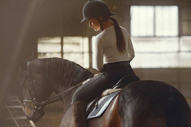Fille élégante dans une ferme avec un cheval