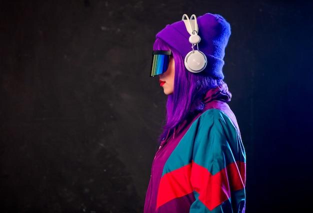 Fille élégante dans des lunettes cyber punk et survêtement avec des écouteurs sur un mur sombre