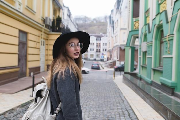 Fille élégante dans un manteau et un chapeau se promène dans la vieille ville et regarde la caméra. belle femme voyage