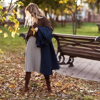 Fille élégante dans un parc en automne dans un pull marron et une jupe à carreaux.