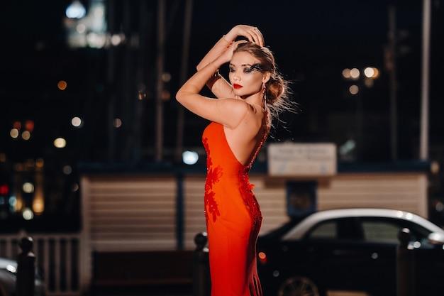 Une fille élégante dans une robe de soirée rouge dans les rues de la ville de nuit de marseille.une femme dans une robe de soirée rouge en france.