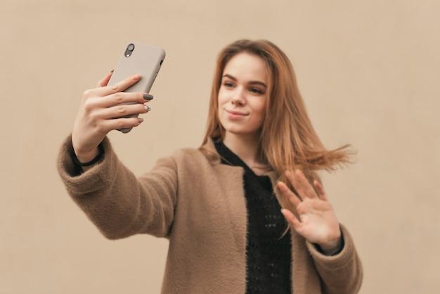 Fille élégante dans des vêtements chauds prend le printemps selfie sur le fond du mur beige