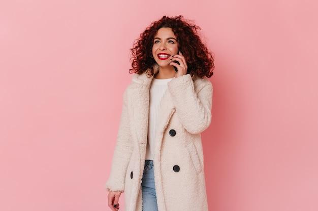 Fille élégante en éco-manteau et jeans parlant au téléphone. femme aux lèvres rouges et sourire blanc posant sur l'espace rose.
