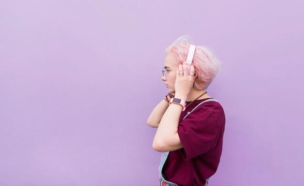 Fille élégante écoute de la musique dans des écouteurs roses sur fond violet