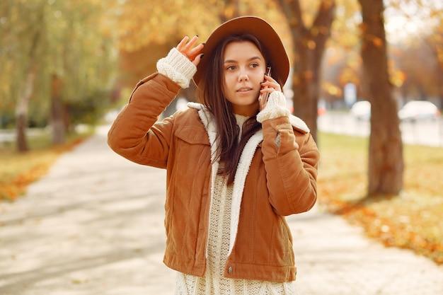 Fille élégante et élégante dans un parc en automne