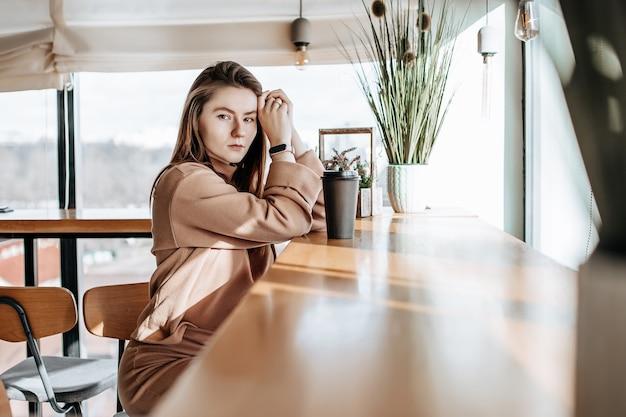 Une fille élégante est assise dans un café et boit du café. café à emporter dans un gobelet en carton. femme aux cheveux roux dans un costume chaud beige dans une ambiance cosy. intérieur moderne. passe-temps calme et agréable