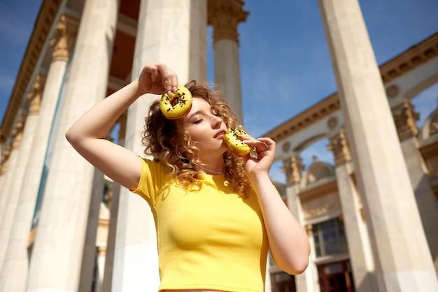 Fille élégante avec de longs cheveux bouclés pose positivement tenant des beignets frais prêts à déguster des bonbons