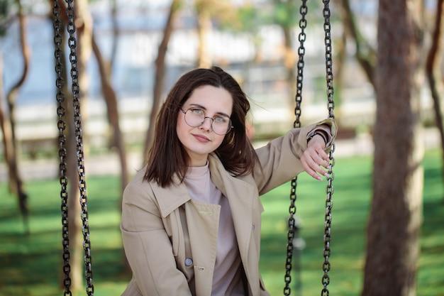 Fille élégante avec des lunettes, à l'extérieur. adolescente sur une balançoire, beau portrait.