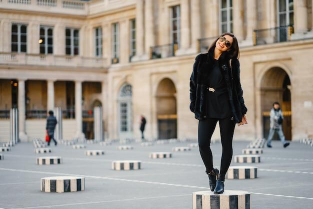 Fille élégante marchant dans les rues de paris au printemps
