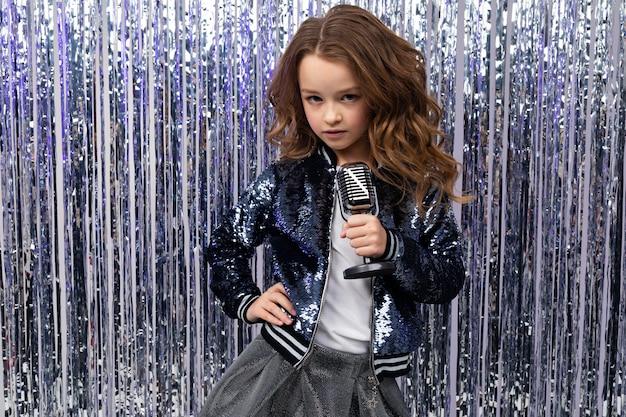 Fille élégante avec un microphone rétro à la main sur un mur de vacances brillant
