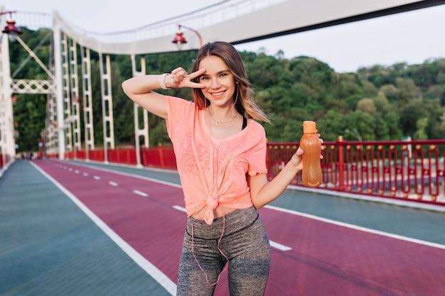 Fille élégante en pantalon de sport gris drôle posant après l'entraînement. portrait en plein air de jocund jeune femme se détendre au stade.