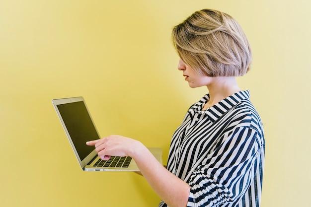 Fille élégante pointant sur l'écran d'un ordinateur portable