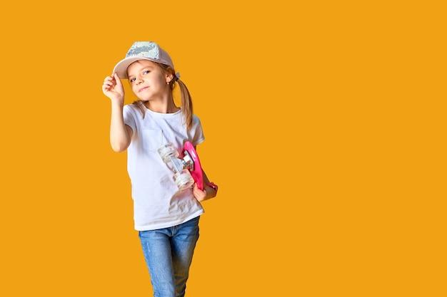 Fille élégante portant un t-shirt blanc, un jean bleu et une casquette rose, tenant une planche à roulettes sur un espace jaune