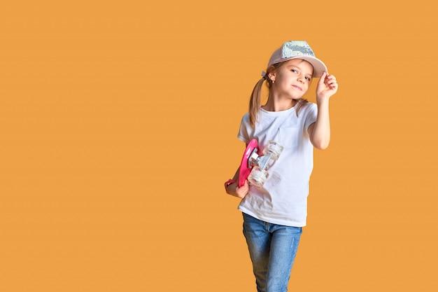 Fille élégante portant un t-shirt blanc, un jean bleu et une casquette rose, tenant une planche à roulettes sur fond jaune
