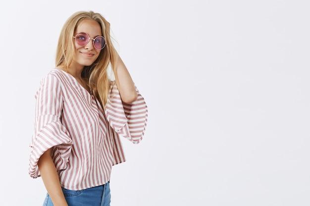 Fille élégante posant contre le mur blanc avec des lunettes de soleil