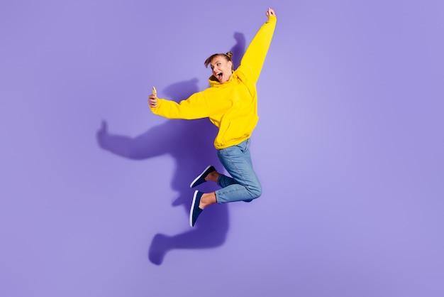 Fille élégante posant contre le mur violet