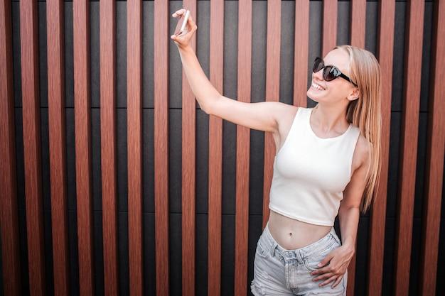 Fille élégante prend selfie. elle regarde au téléphone à travers des lunettes et sourit.
