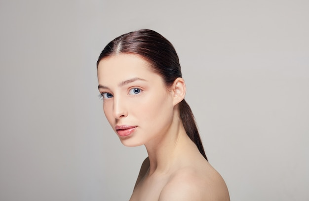 Une fille élégante et sophistiquée avec des lèvres charnues, des cheveux brun foncé et une peau propre et délicate et radieuse sur le gris. femme bien soignée. spa.