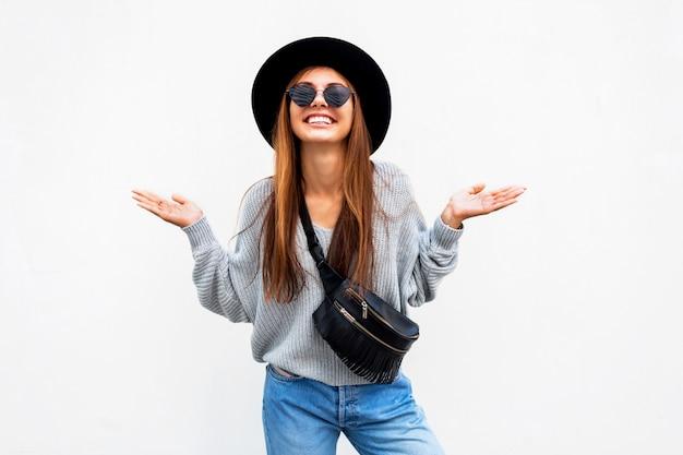 Fille élégante sortie réussie avec un sourire candide posant sur un mur urbain blanc