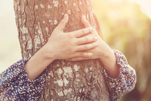 Fille embrassant l'arbre