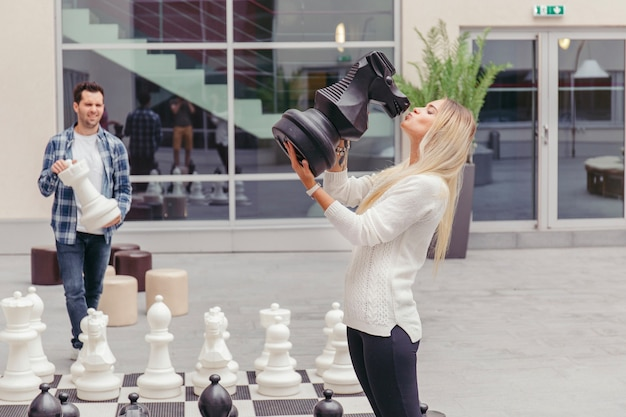 Fille embrassant le cheval d'échecs par échiquier
