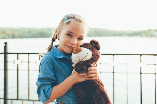 Fille embrassant un mignon ours en peluche