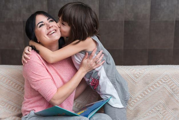 Fille embrassant sa mère avec un livre sur la joue