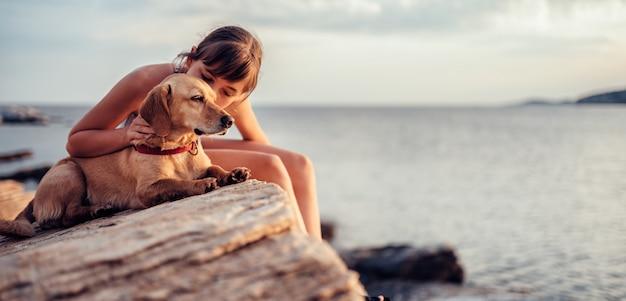 Fille embrassant son chien assis sur le rocher au bord de la mer