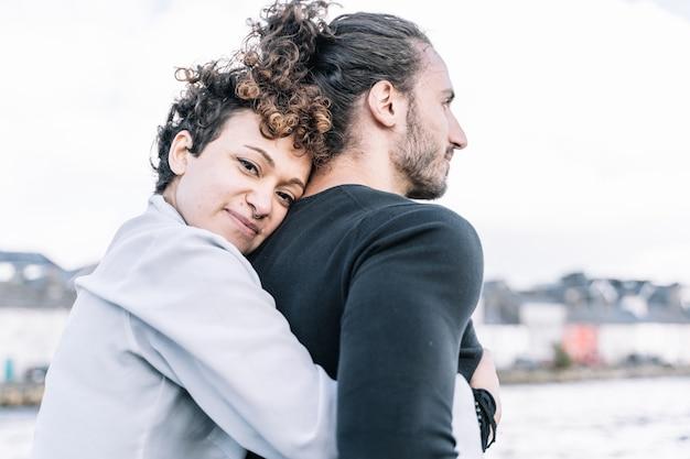 Fille embrassant son partenaire avec la mer floue