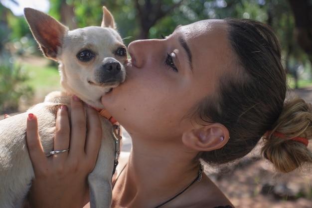 Une fille embrasse un chien chihuahua au parc