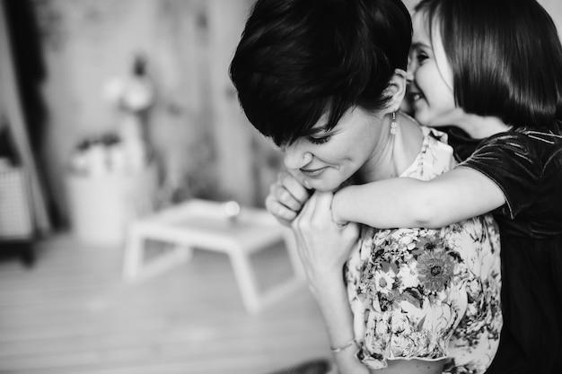 La fille embrasse sa mère dans la chambre