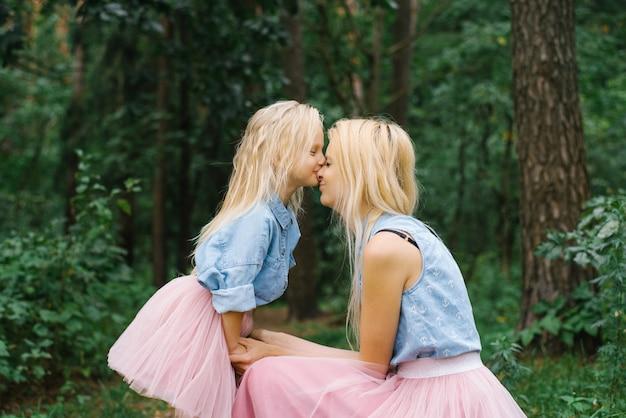 La fille embrasse sa mère sur le nez et sourit. fête des mères