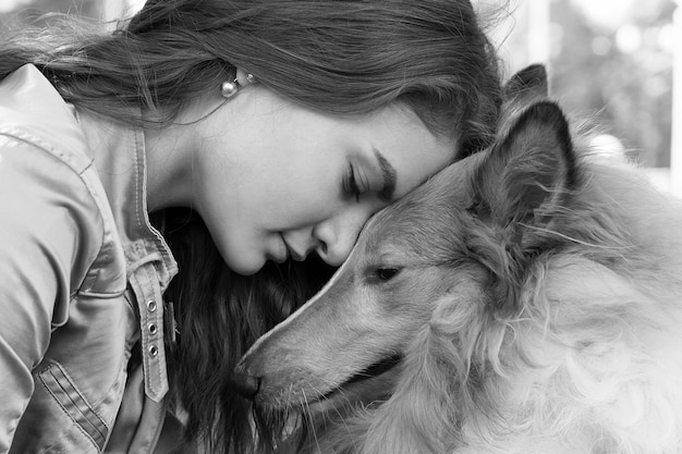 Fille embrasse son chien collie